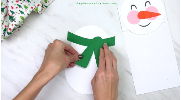 Hands gluing scarf onto paper bag snowman body