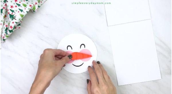 Hands gluing carrot nose on paper bag snowman craft