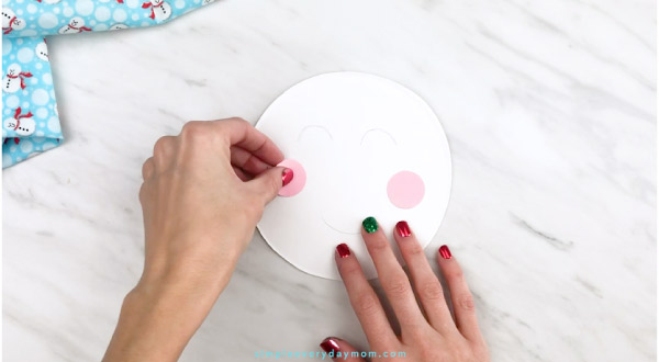 Hands gluing cheeks onto paper plate snowman head