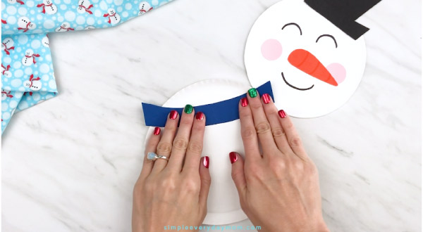 Hands gluing scarf onto paper plate snowman