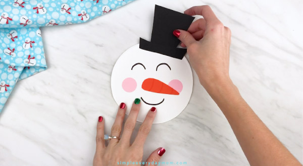 Hands gluing hat onto paper plate snowman