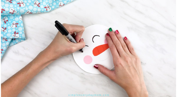 Hands drawing snowman eyes onto paper plate snowman