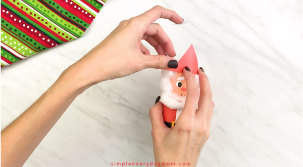 Hands gluing hat to toilet paper roll Santa craft