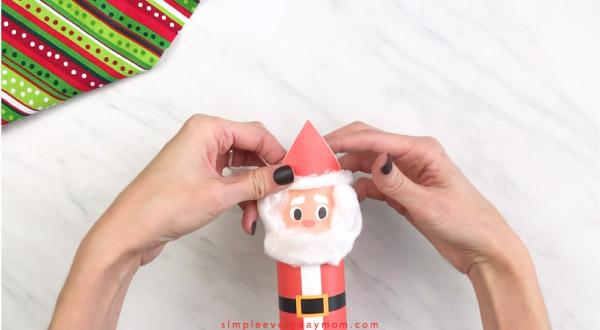 Hands gluing cotton ball fluff to Santa hat