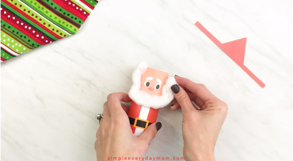 Hands gluing cotton bear to toilet paper roll Santa craft