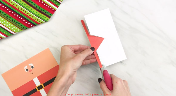 Hands cutting red paper Santa hat out