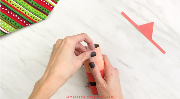 Hands taping toilet paper roll Santa craft onto tube