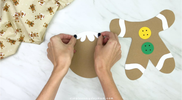 hand gluing icing hair to paper bag gingerbread craft