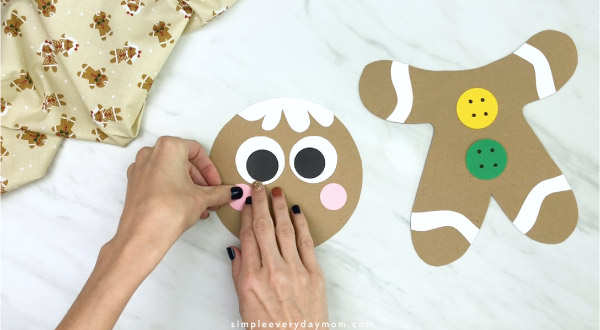 hand gluing cheeks to paper bag gingerbread craft