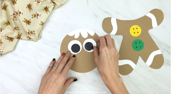 hand gluing eyes to paper bag gingerbread craft