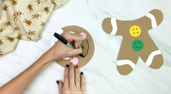 hands drawing a smile on paper bag gingerbread man craft