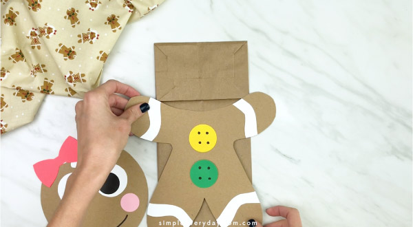 hand gluing body onto paper bag gingerbread craft