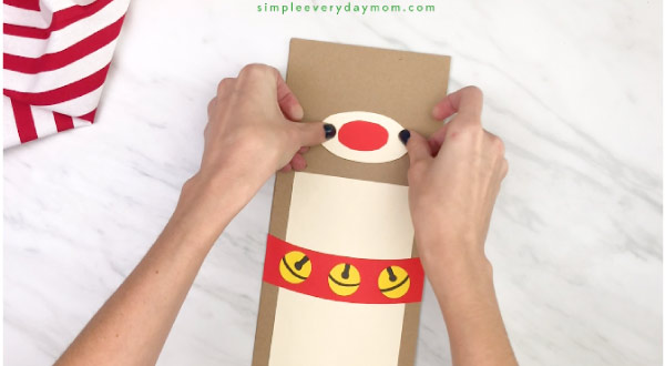 hand gluing nose onto paper bag reindeer craft