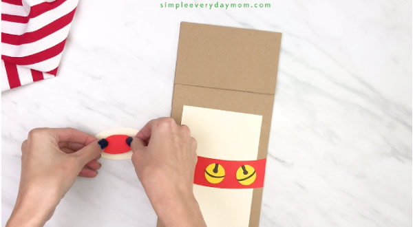 hands gluing paper nose onto muzzle for paper bag reindeer craft
