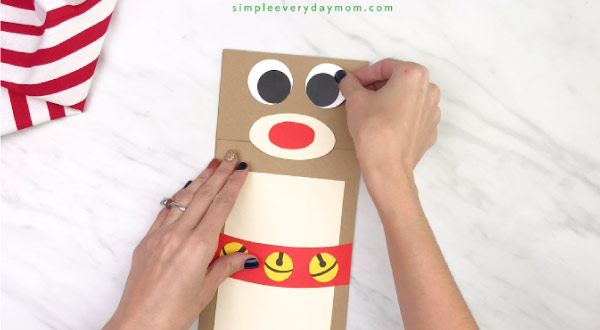 hand gluing eyes onto paper bag reindeer craft
