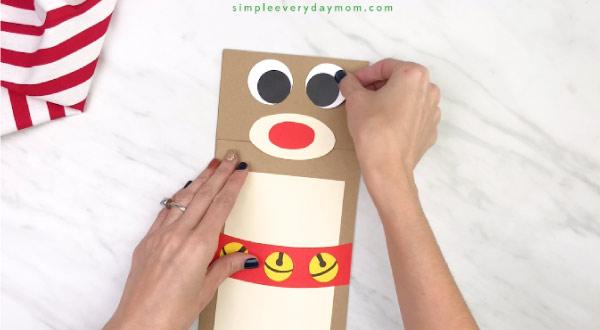 hand gluing eyes onto paper bag reindeer craft