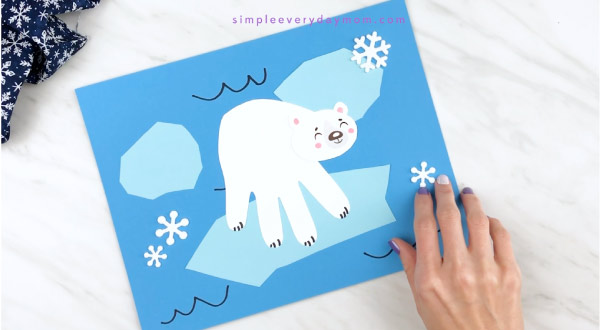 Hands gluing snowflake stickers onto polar bear craft
