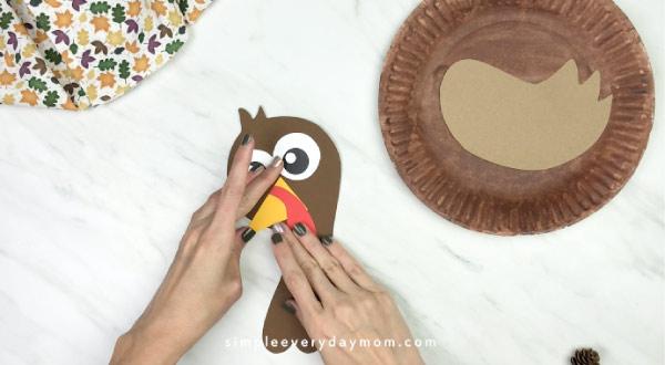 hands gluing beak onto paper plate turkey craft