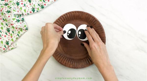 hand gluing eyes onto paper plate reindeer craft
