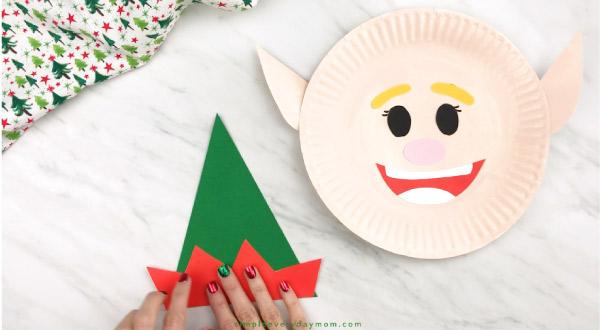 hands gluing elf hat together for paper plate elf craft