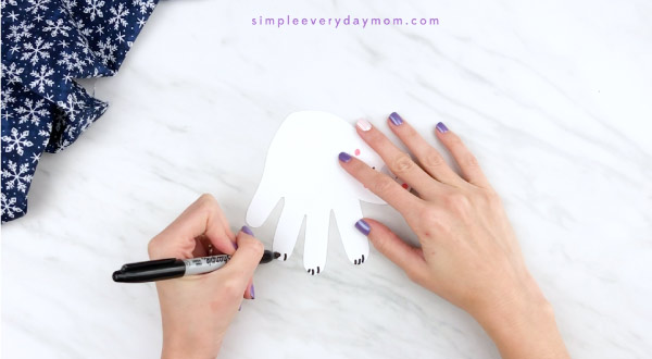 Hands drawing claws onto handprint polar bear