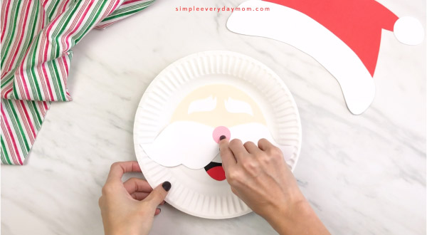 hands gluing nose onto paper plate Santa craft