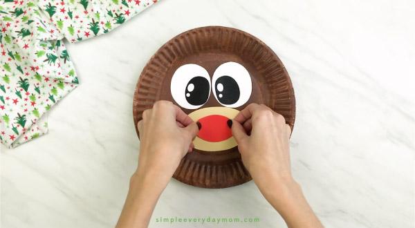 hand gluing nose onto paper plate reindeer craft