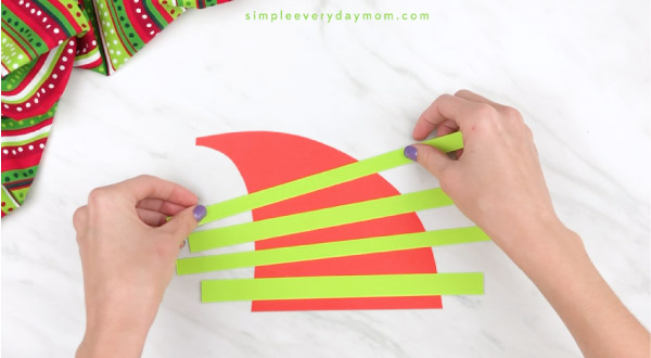 Hands gluing stripes onto elf headband craft