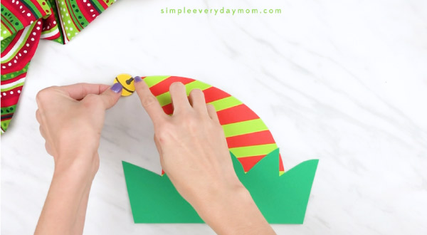 Hands gluing bell onto elf headband craft