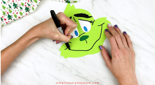Hands drawing mouth onto grinch headband craft
