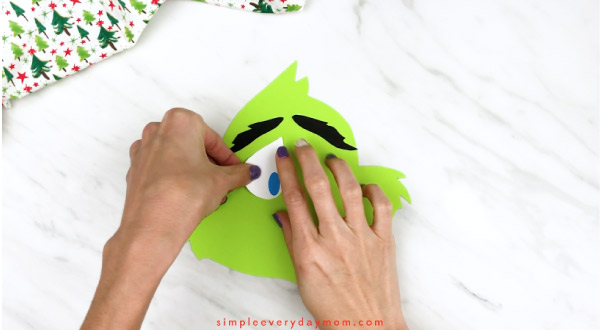 Hands gluing eyes onto grinch face