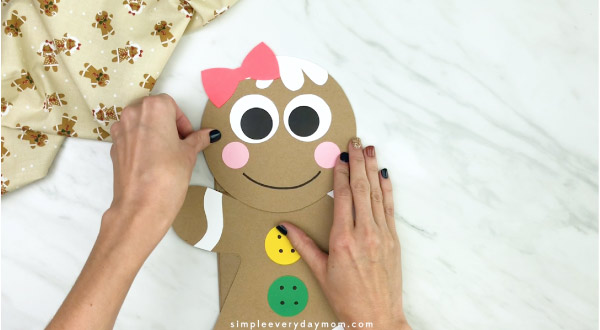 hand gluing head to paper bag gingerbread craft