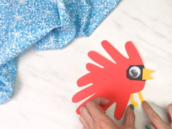 hands gluing legs onto handprint cardinal craft