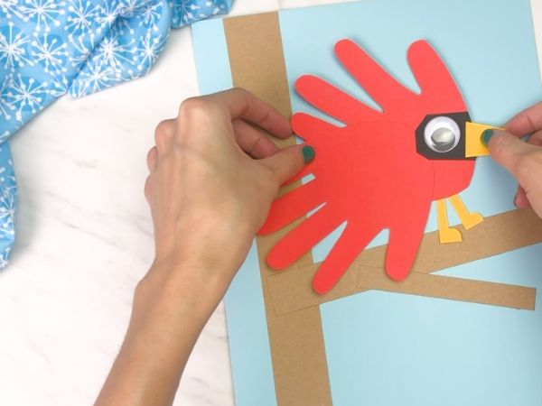 hands gluing handprint cardinal onto paper tree
