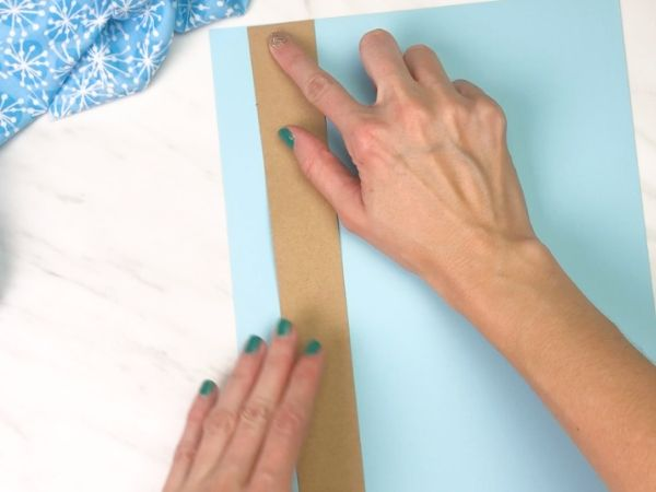 hands gluing brown paper onto blue paper