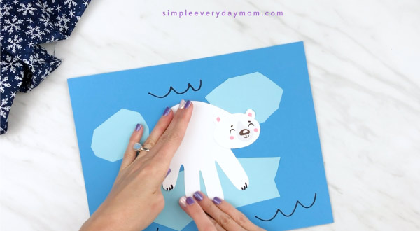 Hands gluing handprint polar bear onto blue paper