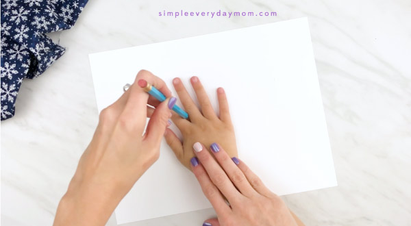 Hands tracing child hand onto white paper
