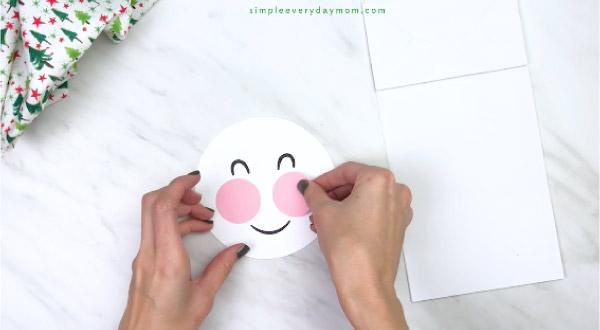 Hands gluing cheeks on paper bag snowman craft