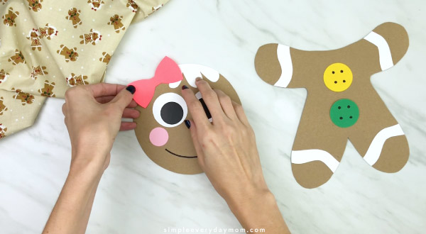 hand gluing bow to paper bag gingerbread craft