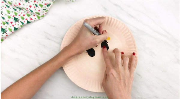 hands drawing eyelashes onto paper plate elf craft