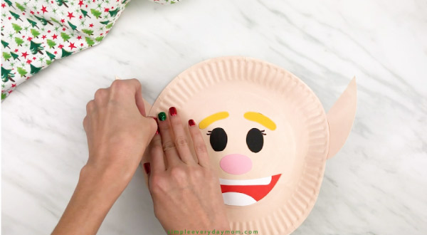 hands gluing ears onto paper plate elf craft