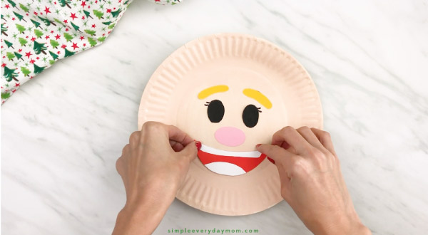 hands gluing mouth onto paper plate elf craft