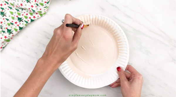 hands painting paper plate peach
