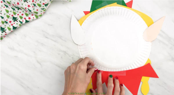 hands taping elf collar to back of paper plate elf craft