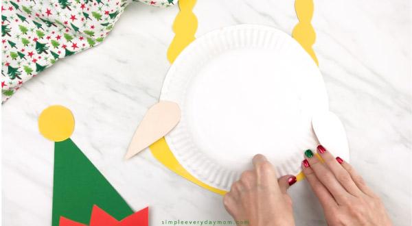 hands taping girl elf hair onto paper plate elf