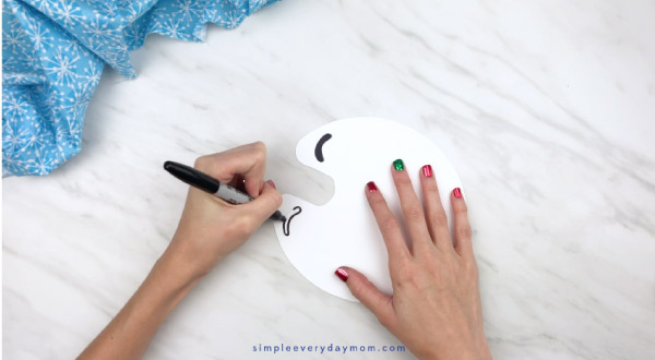 Hands drawing on penguin eyes