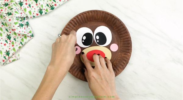 hand gluing cheeks onto paper plate reindeer craft