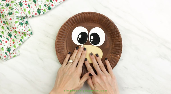 hand gluing muzzle onto paper plate reindeer craft