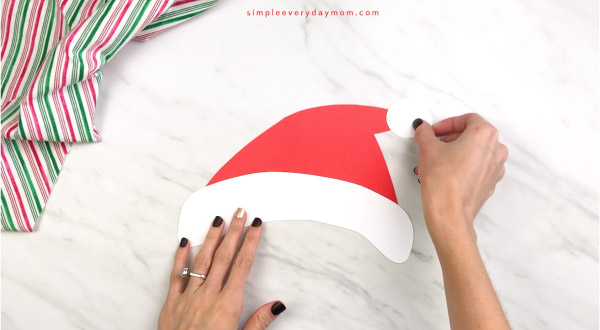 hand gluing pom to end of paper santa craft