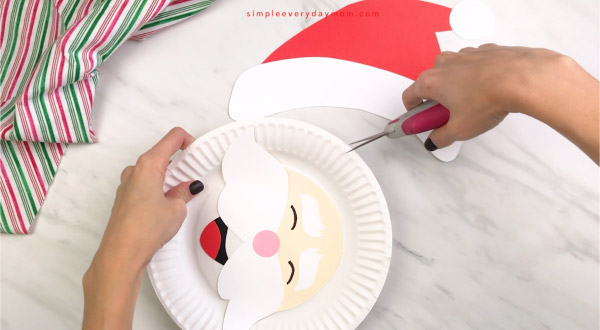 hands cutting top of Santa paper plate craft